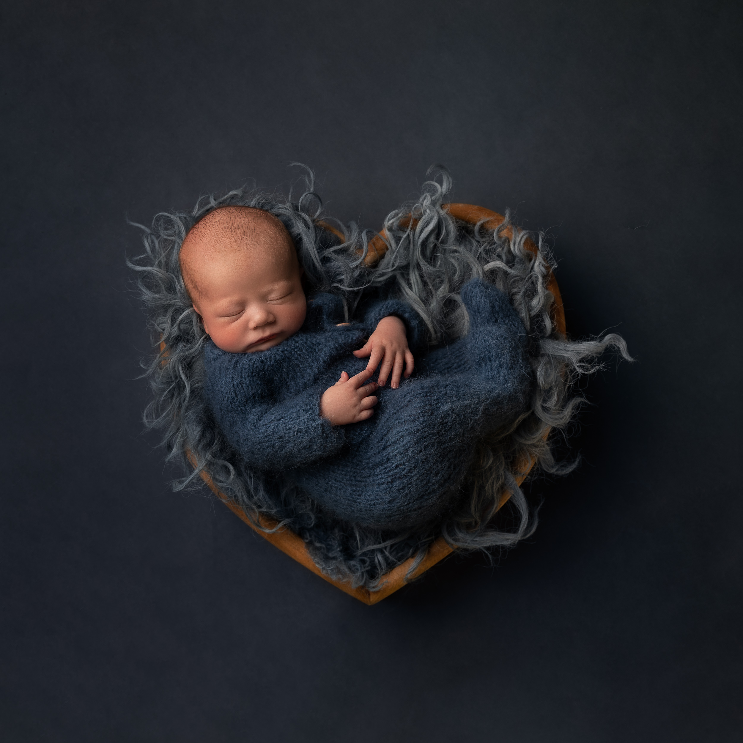 Blue themed newborn baby photo in a heart shape by Cheshire newborn photographer in Sandbach