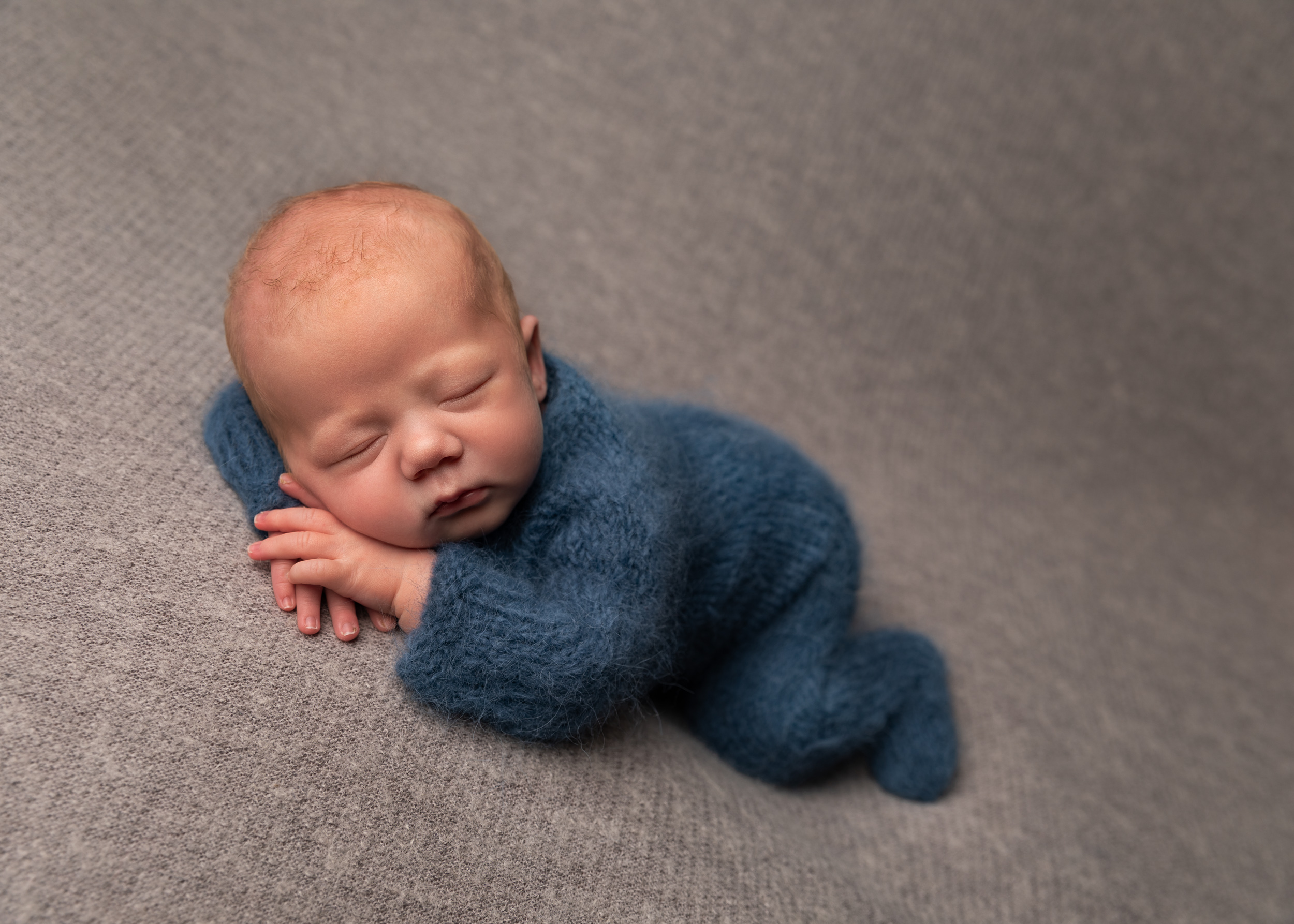 Posed newborn baby in grey and blue colour scheme by Cheshire newborn photographer in Sandbach