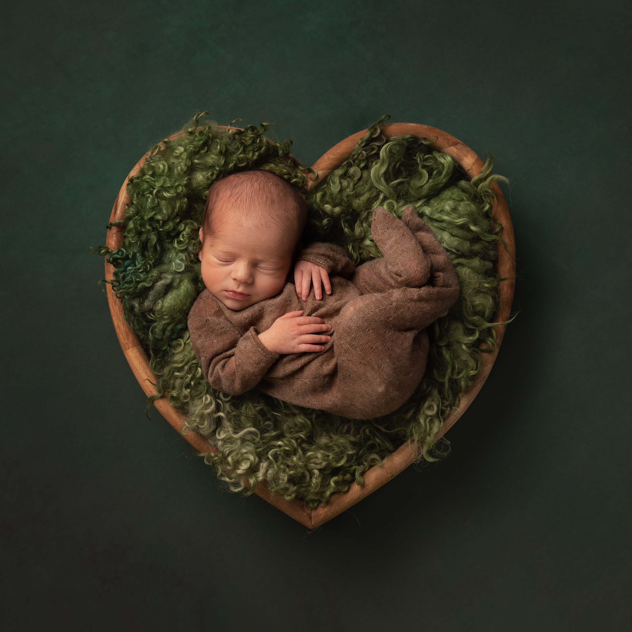 Baby in a heart prop with green colour scheme by Cheshire newborn photographer in Sandbach