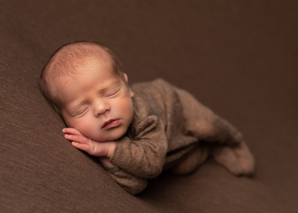 side posed newborn baby all in brown by Cheshire newborn photographer in Sandbach
