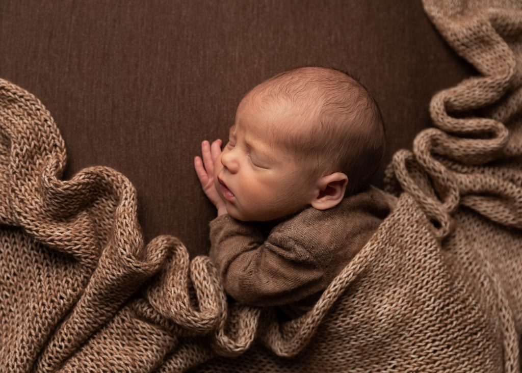 cosy warm newborn baby posed with wrap draped over by Cheshire newborn photographer in Sandbach