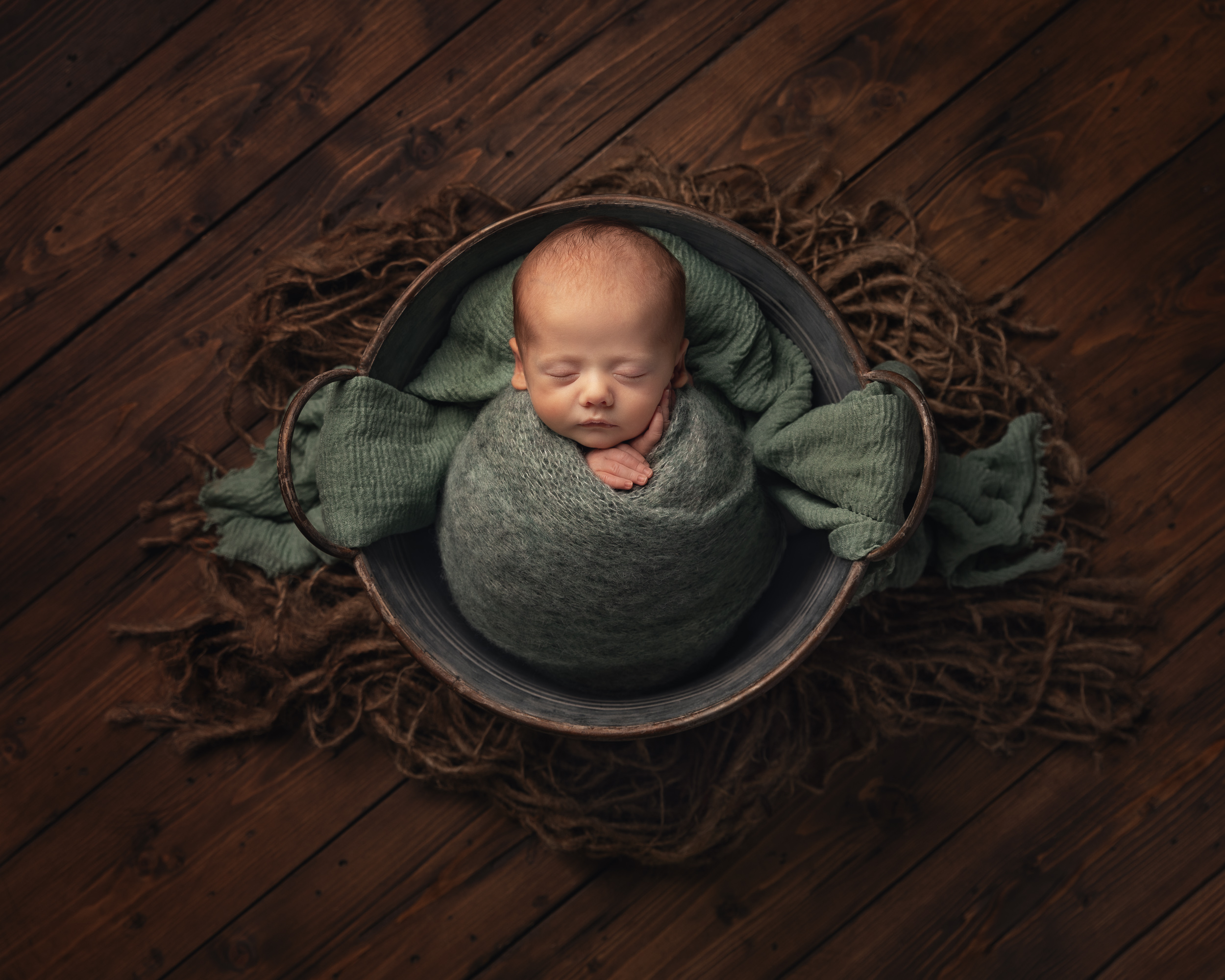Beautiful newborn baby wrapped and in a bucket with their little hands out by Cheshire newborn photographer in Sandbach