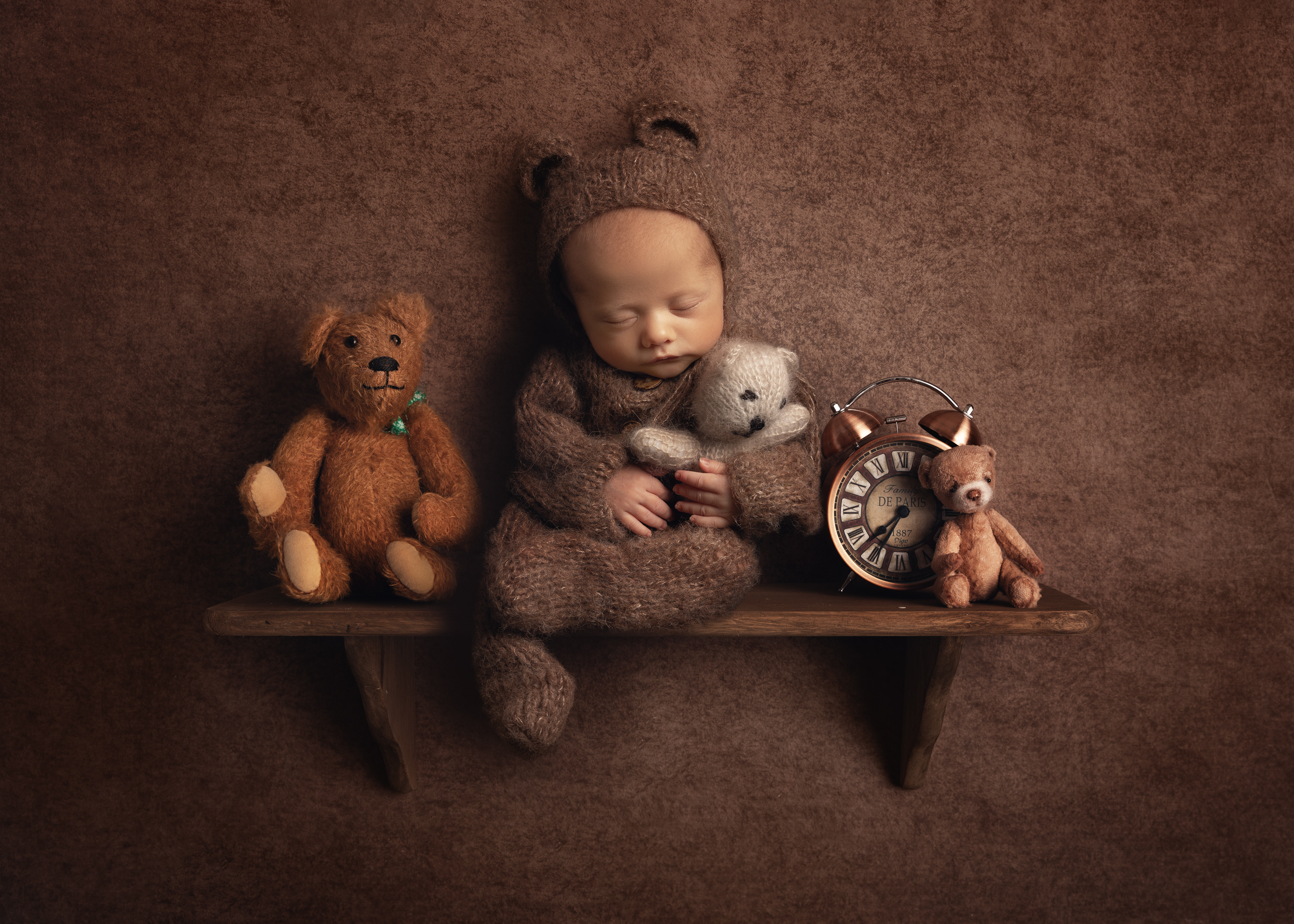 newborn baby dressed as a teddy bear sitting on a shelf with other bears by Cheshire newborn photographer in Sandbach