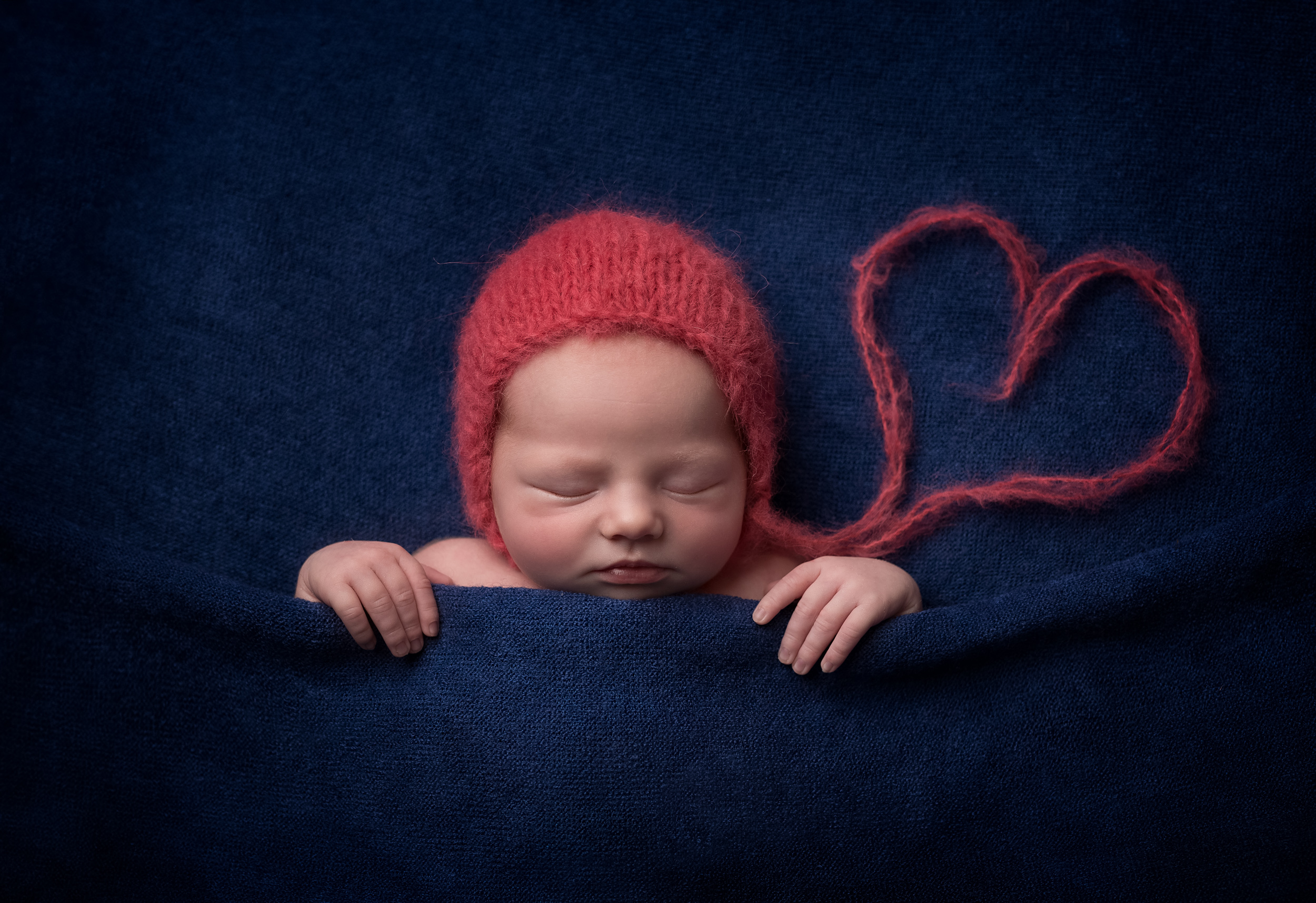 Sleeping newborn baby with bonnet on and heart in striking image by Cheshire newborn photographer in Sandbach
