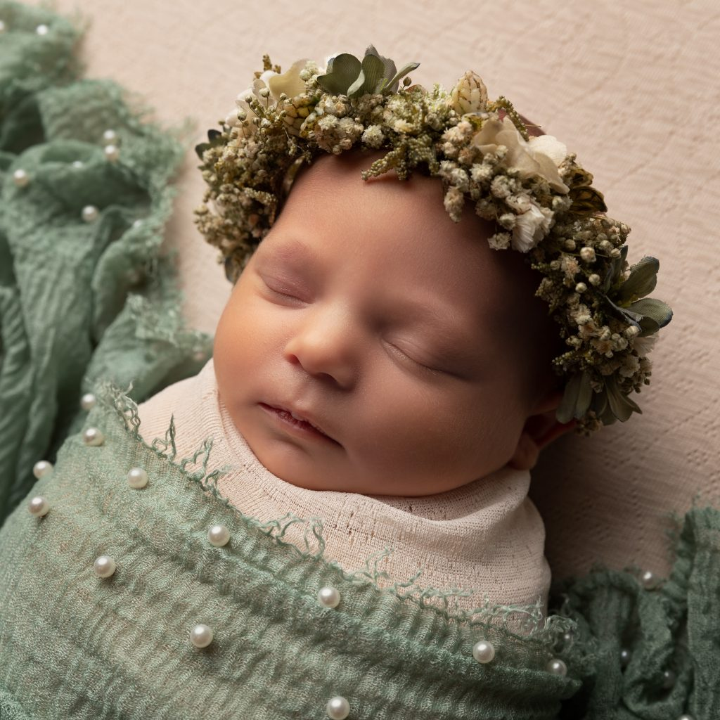 newborn baby wrapped in cream and green with pearls and halo by Cheshire newborn photographer in Sandbach