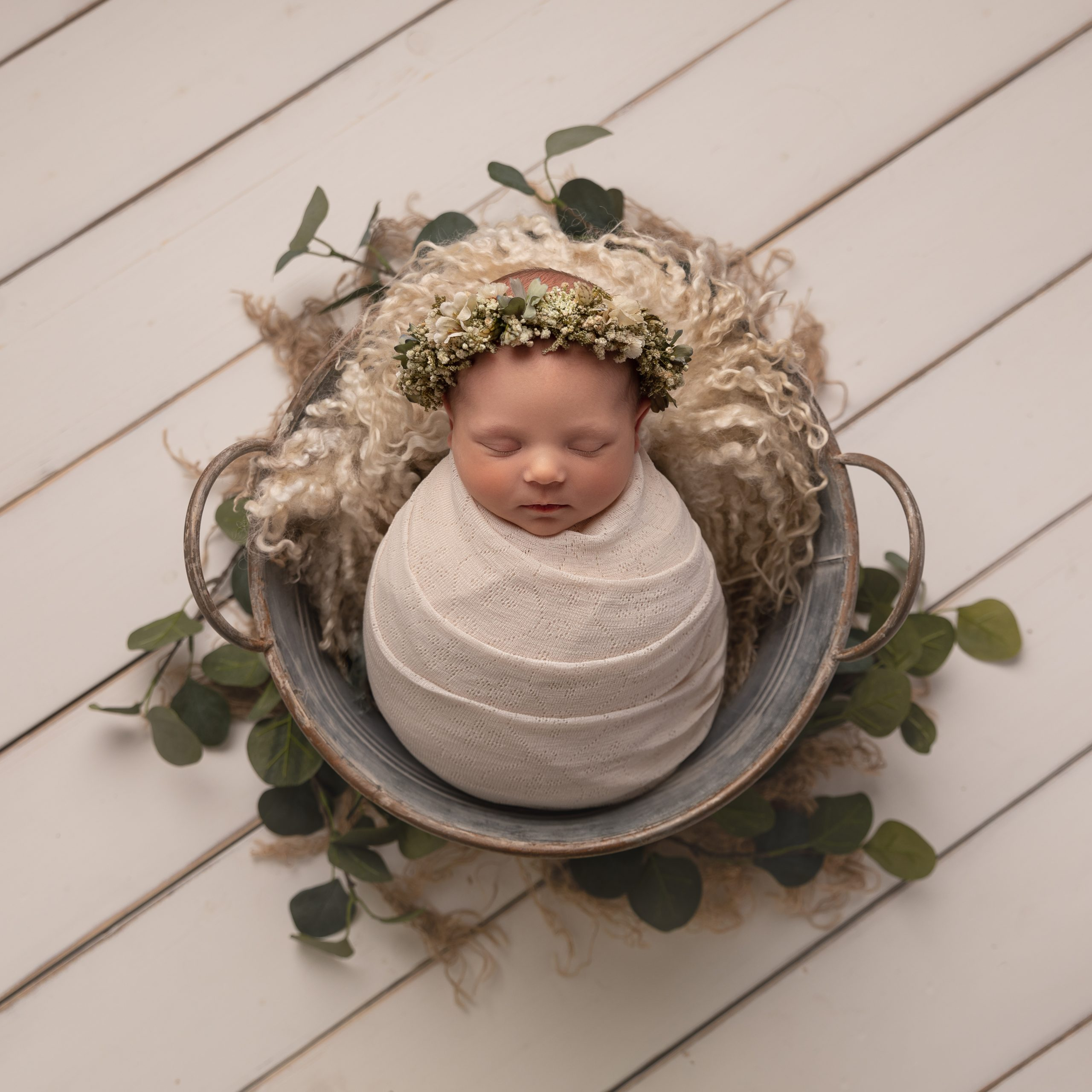 Newborn baby wrapped in white cotton and placed in a metal bucket with stunning headband Cheshire Newborn Photographer in Sandbach