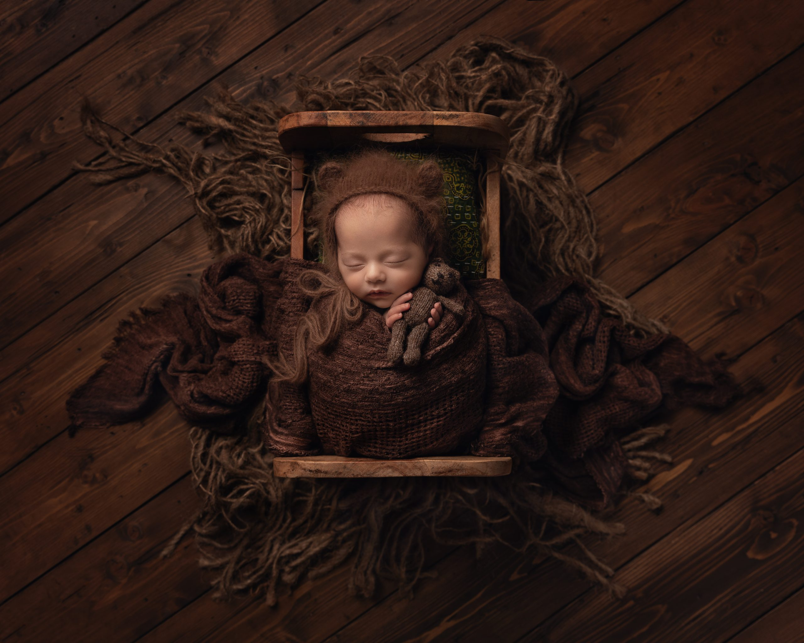 Wrapped newborn baby holding a teddy in a wooden bed